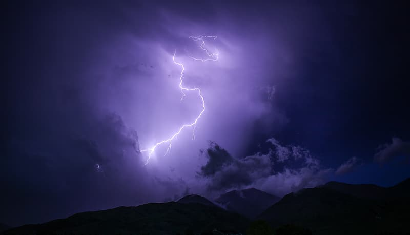 Lightning bolt over mountain during nighttime
