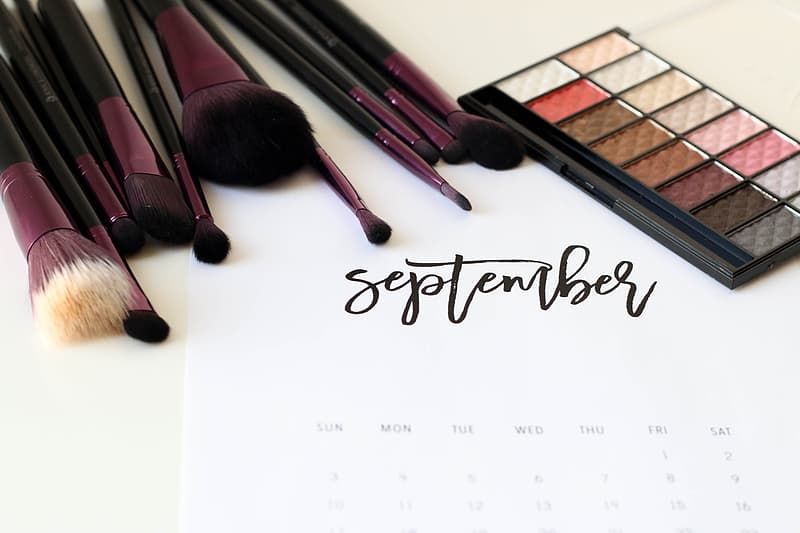 White calendar poster with makeup brushes and eyeshadow palette