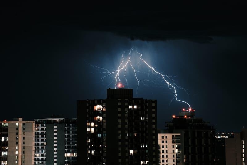 Lightning striking buildings during nighttime