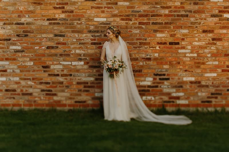 Woman in white wedding gown holding bouquet of flowers