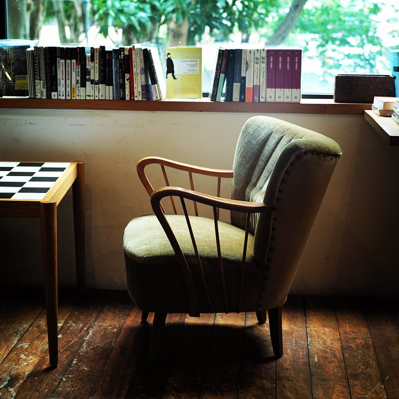 Gray sued armchair beside books